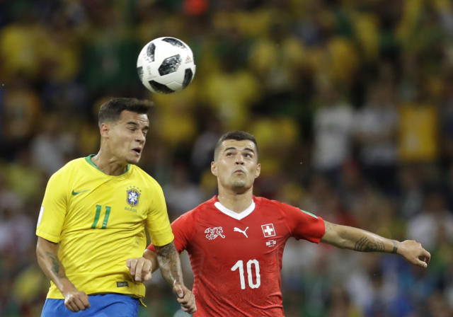 Brazil's Philippe Coutinho, left, and Switzerland's Granit Xhaka jump for the ball during the group E match between Brazil and Switzerland at the 2018 soccer World Cup in the Rostov Arena in Rostov-on-Don, Russia, Sunday, June 17, 2018. (AP Photo/Themba Hadebe)