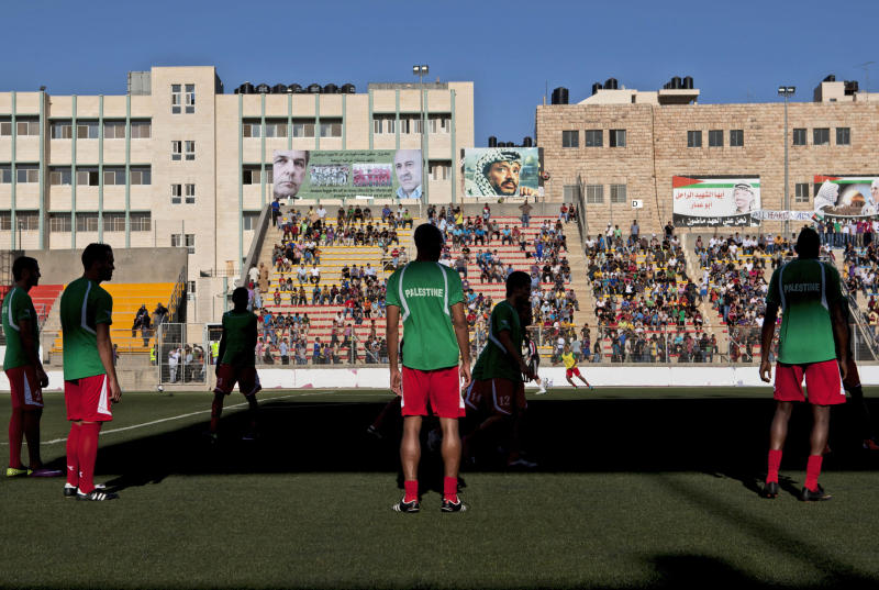 Palestinian soccer players warm up before  World Cup qualifier  game against Thailand in West Bank city of Ramallah, Thursday, July 28, 2011. The Palestinians' hopes of a World Cup place were dashed on Thursday when their team could only draw 2-2 with Thailand, who made it through to the third round of Asian qualifiers with a 3-2 aggregate victory.  For the Palestinians, the loss marked a disappointing end to a World Cup qualifying campaign that had become a symbol of nation building.(AP Photo/Sebastian Scheiner)