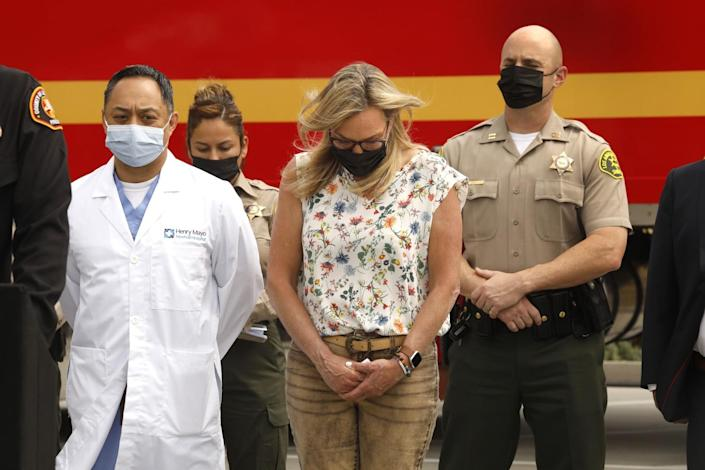 A woman stands outside alongside a doctor in a white coat and two deputies. They all bow their heads.