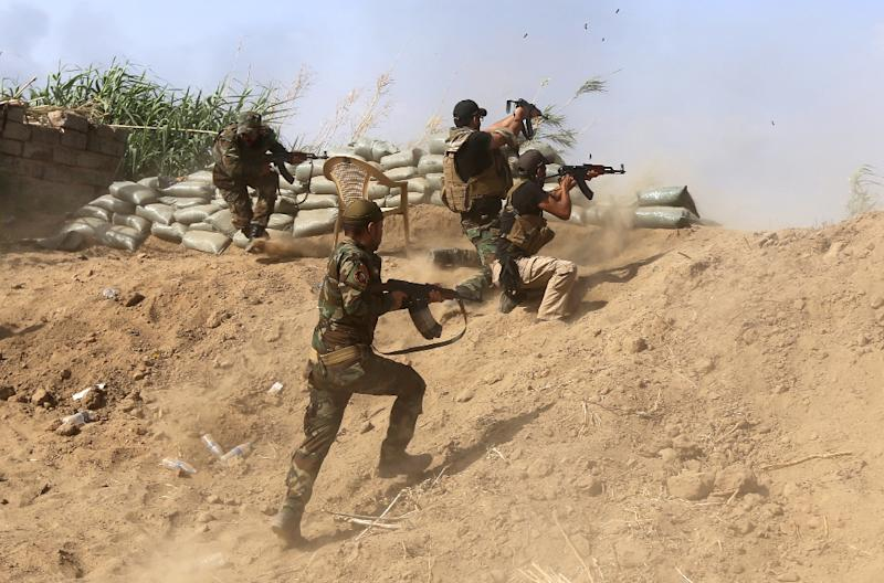 Iraqi Sunni fighters battling Islamic State group jihadists alongside government forces firing their weapons on the outskirts of Iraq's Baiji oil refinery on May 25, 2015