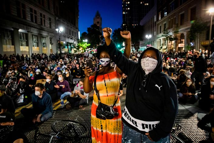 """Demonstrators raise their fists during a """"Sit Out the Curfew"""" protest in Oakland, California, on June 3, 2020, after the death of George Floyd, who was murdered in Minneapolis while in police custody. It was the ninth straight night of protests around the country, with thousands chanting against racism and police brutality. (Photo by Philip Pacheco / AFP)"""