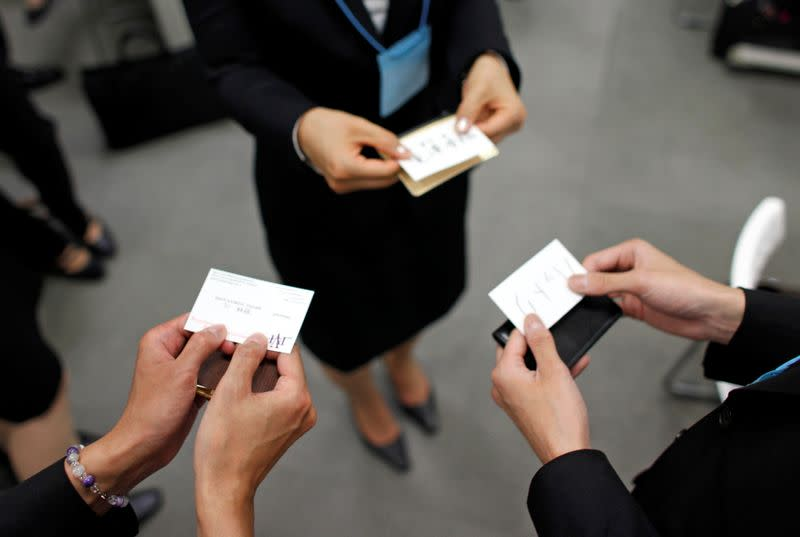 FILE PHOTO : Japanese job-hunting students dressed in suits practice swapping business cards during a business manners seminar at a placement centre in Tokyo