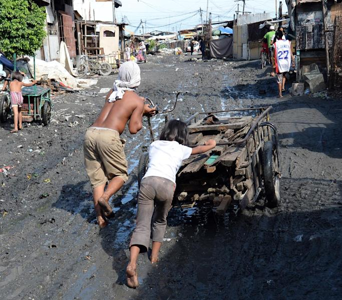 A father and his daughter push a rickshaw loaded with used wood to be smelted as charcoal in the slums of Manila on June 9, 2013 (AFP Photo/Ted Aljibe)