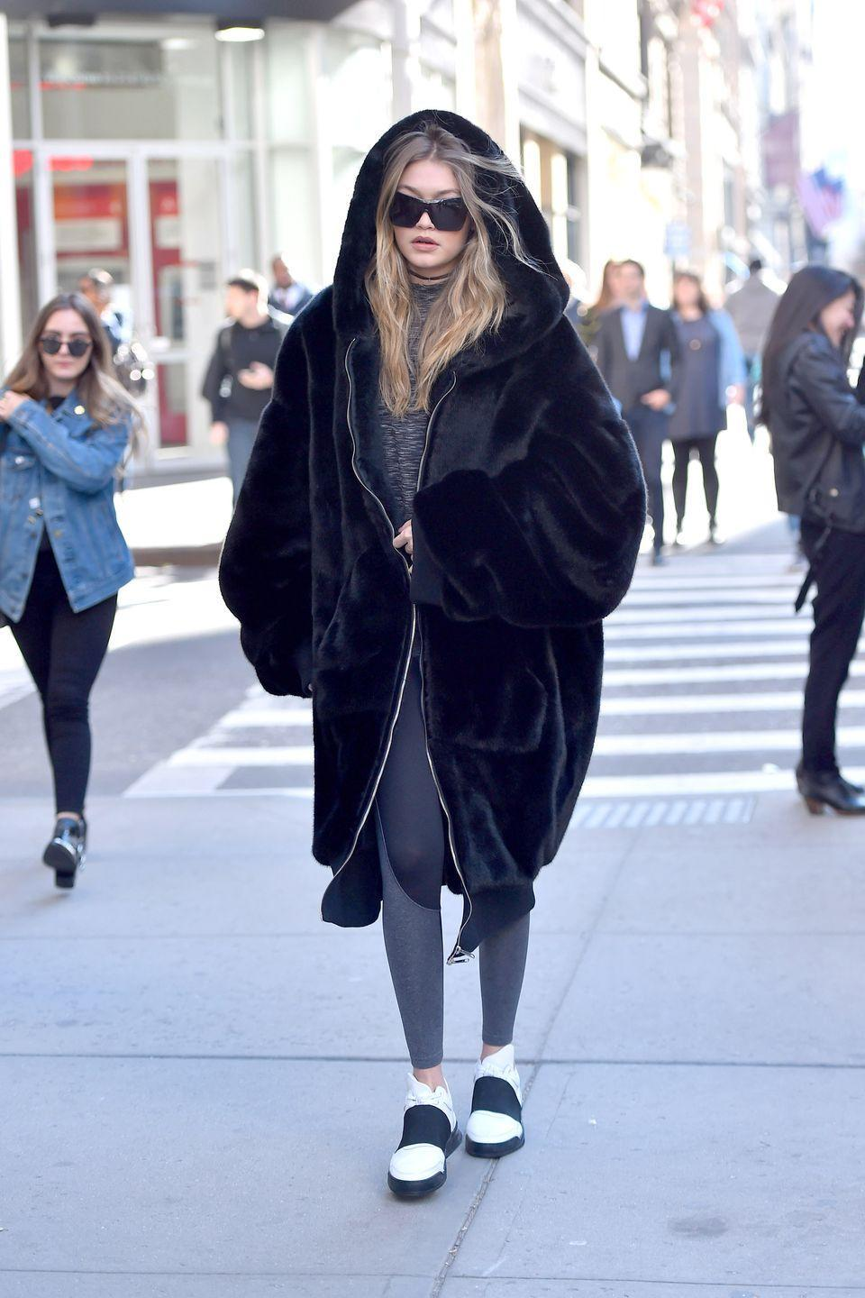 <p>Hadid looked cozy hitting the streets of New York, topping her black + white athleisure look with an oversized furry coat. </p>