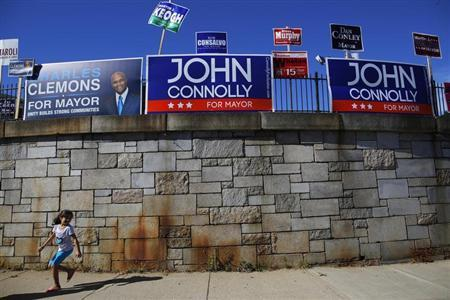 A girl runs under campaign signs outside a polling station in Boston, Massachusetts