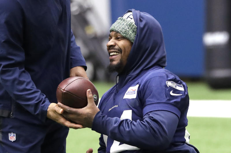 Seattle Seahawks running back Marshawn Lynch smiles during warmups at the NFL football team's practice facility Tuesday, Dec. 24, 2019, in Renton, Wash. When Lynch played his last game for the Seahawks in 2016, the idea of him ever wearing a Seahawks uniform again seemed preposterous. Yet, here are the Seahawks getting ready to have Lynch potentially play a major role Sunday against San Francisco with the NFC West title on the line. (AP Photo/Elaine Thompson)