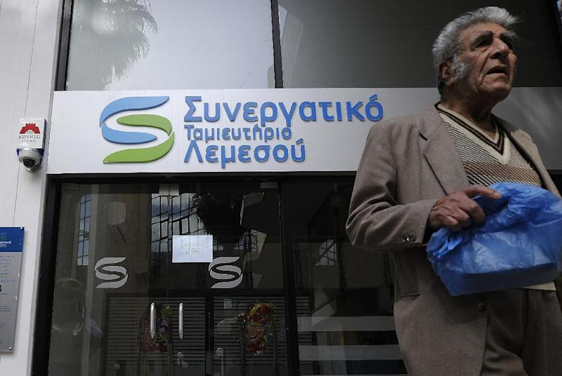 An elderly man passes by a cooperative bank in Limassol, Cyprus, Saturday, March 16, 2013. Many rushed to the cooperative banks which are open Saturdays in Cyprus, after learning that the terms of a bailout deal that the cash-strapped country hammered out with international lenders, includes a one-time levy on bank deposits. The move, decided in an extraordinary meeting of the finance ministers of the 17-nation euro zone in the early hours Saturday, is a major departure from established policies. (AP Photo/Pavlos Vrionides)