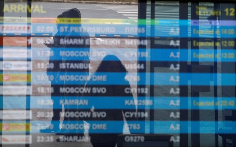 FILE PHOTO: People are seen reflected in a flight information board at Kazan airport, where a Tatarstan Airlines Boeing 737 crashed