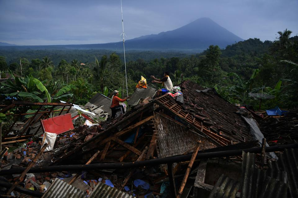 People salvage their belongings from a house damaged by an earthquake in Lumajang, East Java province, Indonesia.