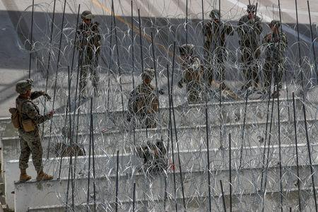 FILE PHOTO: U.S. Marines help to build a concertina wire barricade at the U.S. Mexico border in preparation for the arrival of a caravan of migrants at the San Ysidro border crossing in San Diego, California, U.S., November 13, 2018.   REUTERS/Mike Blake/File Photo