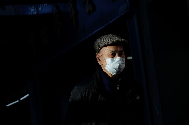 A man wearing a face mask walks through the Chinatown section of San Francisco, California