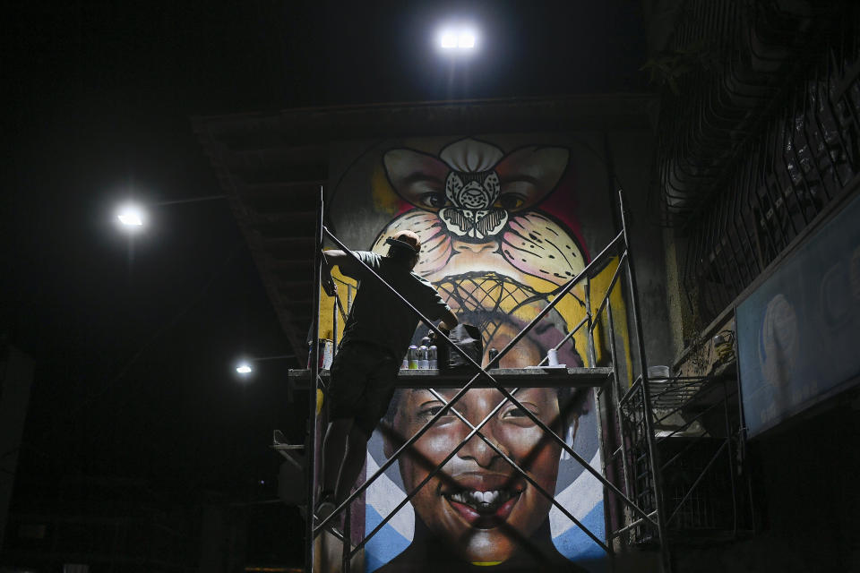Street artist Wolfgang Salazar works into the night on his most recent mural in the Boleita neighborhood of Caracas, Venezuela, Saturday, Jan. 9, 2021. The mural, commissioned by a Caracas restaurant, depicts the smiling face of Venezuelan triple-jump indoor world record setter Yulimar Rojas. (AP Photo/Matias Delacroix)