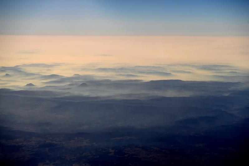 Smoke from bushfires blanket mountain ranges as seen during a commercial flight over northern New South Wales