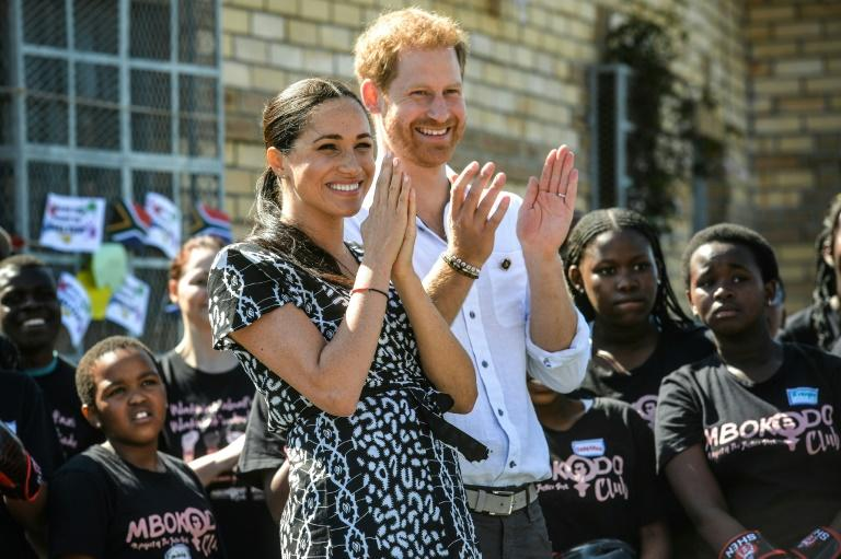 Applause: Prince Harry and Meghan visited a Cape Town rights group fighting gender violence. Rape and murder of women have reached epidemic proportions in South Africa (AFP Photo/Courtney AFRICA)