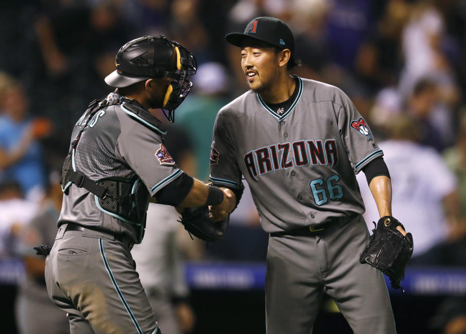 Arizona Diamondbacks catcher Jeff Mathis, left, congratulates relief pitcher Yoshihisa Hirano after he retired Colorado Rockies' Charlie Blackmon for the final out in the ninth inning of a baseball game, Tuesday, Sept. 11, 2018, in Denver. Arizona won 6-3. (AP Photo/David Zalubowski)