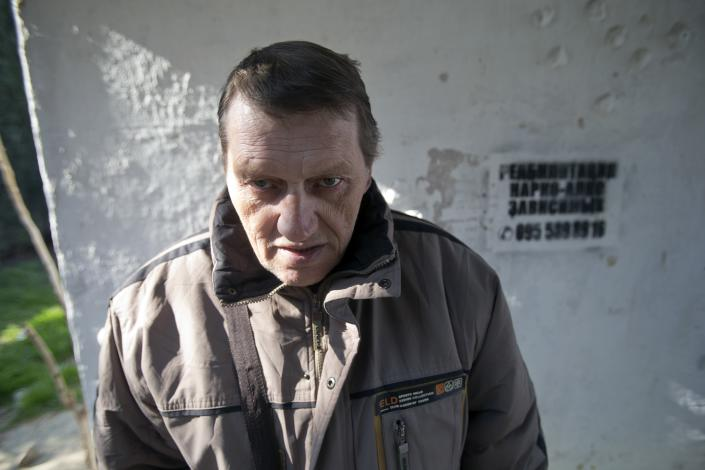 """In this photo taken Tuesday, April 1, 2014, Viktor Levchenko, 36, a patient of treatment for drug addiction, poses at a bus stop with an advert reading """"Rehabilitation of drug and alcohol addicts"""" in Sevastopol, Crimea. Across the Black Sea peninsula, some 800 heroin addicts and other needle-drug users take part in methadone programs, seen as an important part of efforts to curb HIV infections by taking the patients away from hypodermic needles that can spread the AIDS-causing virus. After Russia's annexation of Crimea methadone was banned. The ban could undermine years of efforts to reduce the spread of AIDS in Crimea. (AP Photo/Pavel Golovkin)"""