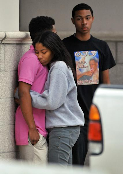 Friends of Jordan Davis comfort each other outside the funeral home where the visitation with Davis' family was taking place at the Hardage-Giddens Funeral Home in Mandarin area of Jacksonville, Fla., late Wednesday afternoon, Nov. 28, 2012. Michael David Dunn has been charged with fatally shooting Davis outside a Jacksonville convenience store following an argument that was triggered because the music coming from the teen's car was too loud. (AP Photo/The Florida Times-Union, Bob Self)