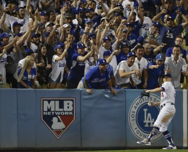 <p>Fans cheer as Los Angeles Dodgers' Enrique Hernandez catches a long fly ball hit by Houston Astros' Josh Reddick during the eighth inning of Game 1 of baseball's World Series Tuesday, Oct. 24, 2017, in Los Angeles. (AP Photo/David J. Phillip) </p>