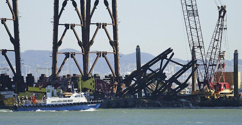 Investigators approach the scene where a crane overturned onto a barge and into San Francisco Bay, seen from Clipper Cove on Treasure Island Thursday, Feb. 21, 2013, in San Francisco. A crane tipped over while working on the new eastern span of the San Francisco-Oakland Bay Bridge on Thursday afternoon, but there were no injuries and nothing leaked into the bay, authorities said. (AP Photo/Ben Margot)