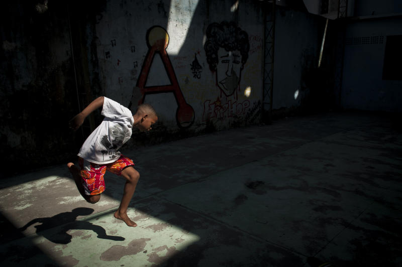 """In this Aug. 3, 2013 photo, a boy jumps in the air and grabs his foot while practicing a step from a dance form called """"passinho,"""" or """"little step,"""" at a makeshift dance studio in the Borel favela, in Rio de Janeiro, Brazil. Passinho is a mix of sambaesque footwork, breakdance handstands, free spins and athletic acrobatics, all set to a music heavy on funk hooks laid over snare beats. (AP Photo/Nicolas Tanner)"""