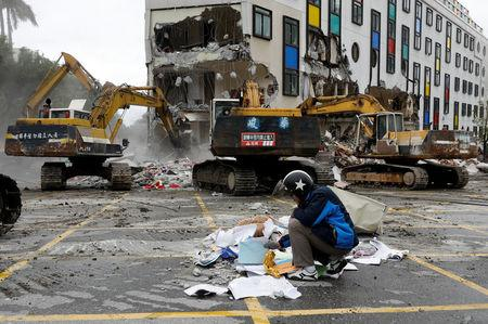 An employee of collapsed Marshal hotel collects items from debris while excavators demolish the hotel after an earthquake hit Hualien