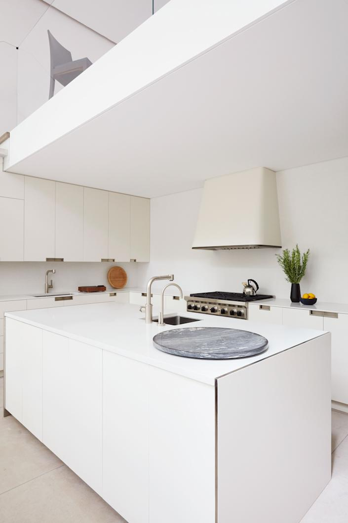 """<div class=""""caption""""> The kitchen features custom cabinetry finished in hand-rubbed lacquer. <a href=""""https://htheophile.com/"""" rel=""""nofollow noopener"""" target=""""_blank"""" data-ylk=""""slk:H. Theophile"""" class=""""link rapid-noclick-resp"""">H. Theophile</a> hardware; custom lacquered metal hood; Wolf range; <a href=""""https://www.dornbracht.com/us"""" rel=""""nofollow noopener"""" target=""""_blank"""" data-ylk=""""slk:Dornbracht"""" class=""""link rapid-noclick-resp"""">Dornbracht</a> sink fittings. </div> <cite class=""""credit"""">Thomas Loof</cite>"""