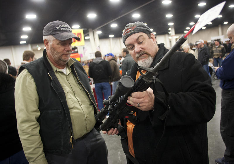 FILE - In a Saturday, Jan. 5, 2013 file photo, gun owners discuss a potential sale of an AR-15, during the 2013 Rocky Mountain Gun Show at the South Towne Expo Center in Sandy, Utah. Nearly six in 10 Americans want stricter gun laws in the aftermath of last month's deadly school shooting in Connecticut, with majorities favoring a nationwide ban on military-style, rapid-fire weapons and limits on gun violence depicted in video games and movies and on TV, according to a new Associated Press-GfK poll. A lopsided 84 percent of adults would like to see the establishment of a federal standard for background checks for people buying guns at gun shows, the poll showed. President Barack Obama was set Wednesday, Jan. 16, 2013 to unveil a wide-ranging package of steps for reducing gun violence expected to include a proposed ban on assault weapons, limits on the capacity of ammunition magazines and universal background checks for gun sales.(AP Photo/The Deseret News, Ben Brewer, File) NO SALES; MAGS OUT; SALT LAKE TRIBINE OUT;  PROVO DAILY HERALD OUT