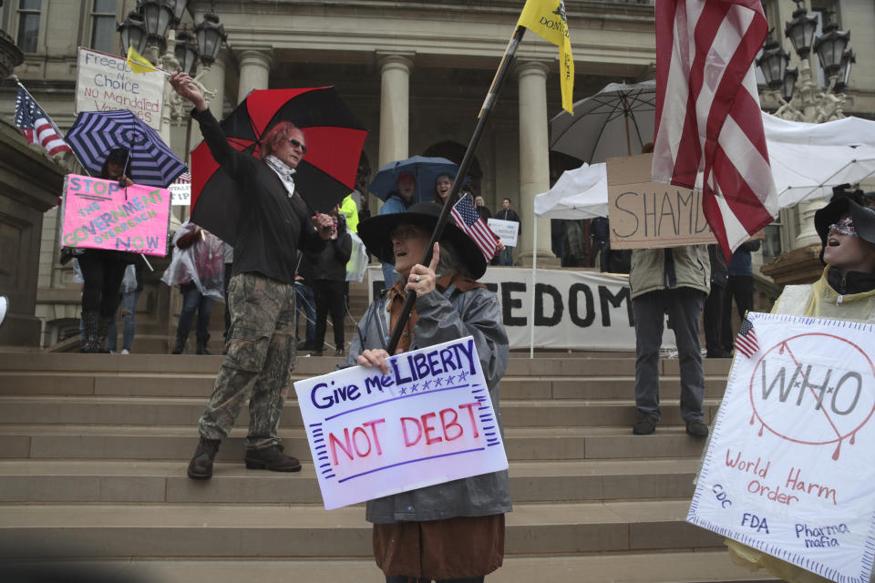Protesters carry signs during a rally at the State Capitol in Lansing, Mich., Thursday, May 14, 2020. (AP Photo/Paul Sancya)