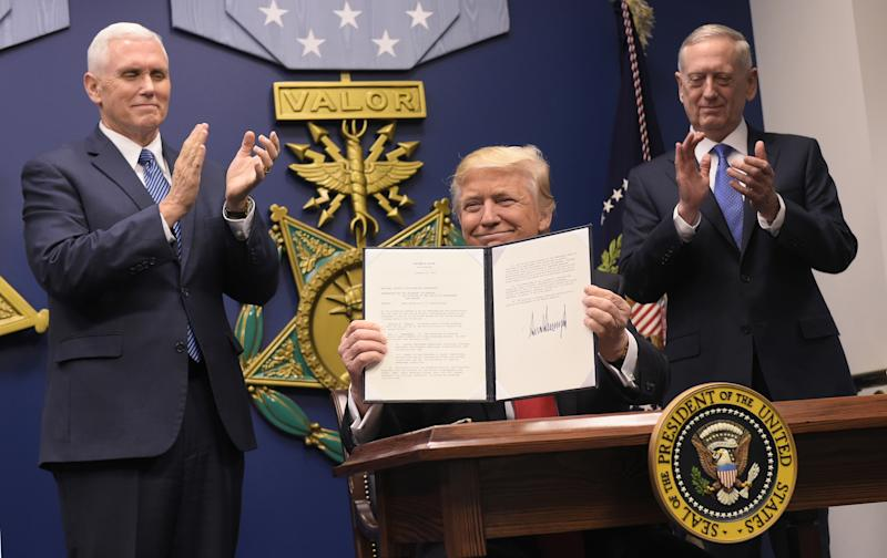 President Trump is flanked by Defense Secretary James Mattis, right, and Vice President Mike Pence after signing executive orders at the Pentagon in January 2017. (Photo: Mandel Ngan/AFP via Getty Images)
