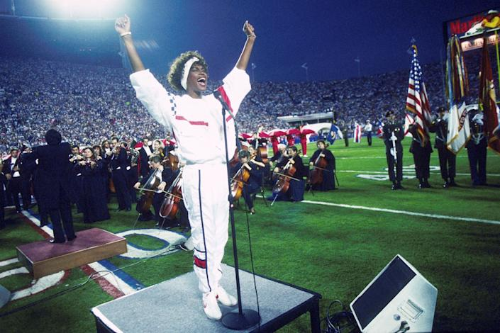 Whitney Houston sings the National Anthem during the pregame show at Super Bowl XXV while tens of thousands of football fans wave tiny American flags in an incredible outburst of patriotism during the Persian Gulf War on Jan. 27, 1991.