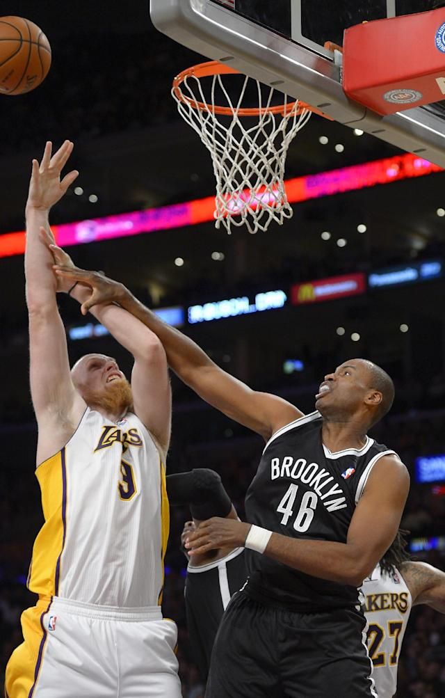 Brooklyn Nets center Jason Collins, right, knocks the ball from the hands of Los Angeles Lakers center Chris Kaman during the second half of an NBA basketball game, Sunday, Feb. 23, 2014, in Los Angeles. The Nets won 108-102. (AP Photo/Mark J. Terrill)