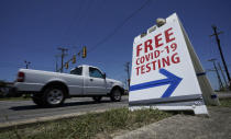 A truck passes a sign for free COVID-19 testing, Friday, Aug. 14, 2020, in San Antonio. Coronavirus testing in Texas has dropped significantly, mirroring nationwide trends, just as schools reopen and football teams charge ahead with plans to play. (AP Photo/Eric Gay)