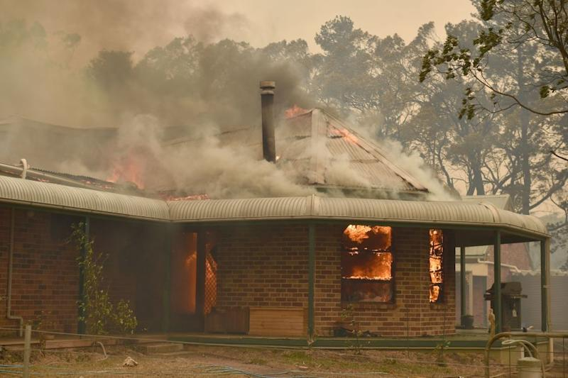 Fire is seen through the glass windows of a home in Balmoral, where a bushfire all but destroyed the town.