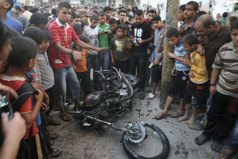 "Palestinians gather a round the wreckage of motorcycle following an Israeli air strike in Rafah, southern Gaza Strip, Sunday, Oct. 7, 2012. Israel's military says it has fired on two Gaza members of an al-Qaida-inspired group identified as having been involved in rocket attacks and an infiltration from Egypt. Palestinians say one man was killed. The military said they were involved in ""extensive terrorist activity,"" including an attack in June where two gunmen crossed into Israel from the Sinai desert and killed a civilian. Israel did not say whether it hit the two. Ashraf al-Kidra, a Palestinian health official in Gaza said one man was killed and another injured Sunday when their motorcycle was hit by aircraft in the south of the Hamas-controlled territory. Israel and Hamas have mostly kept an unwritten truce since a short war over three years ago. Attacks have persisted but at a much lower rate. (AP Photo/Eyad Baba)"
