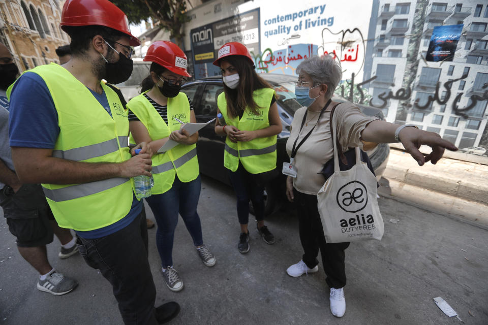 People who volunteered to help clean damaged homes and give other assistance, takes notes from a woman on a street that was damaged by last week's explosion, in Beirut, Lebanon, Tuesday, Aug. 11, 2020. In the absence of the state, acts of kindness and solidarity have been numerous and striking. Many extended a helping hand far beyond their circle of friends or family, taking to social media to spread the word that they have a room to host people free of charge. (AP Photo/Hussein Malla)