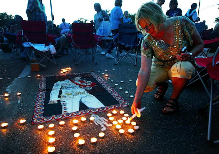 Elvis Presley fan Jill Gibson lights candles outside Graceland, Presley's home, before the annual candlelight vigil on Thursday, Aug. 15, 2013, in Memphis, Tenn. Presley fans from around the world made their annual pilgrimage to Graceland to pay their respects to the rock n' roll icon with a solemn candlelight vigil on the 36th anniversary of his death. (AP Photo/The Commercial Appeal, Nikki Boertman)