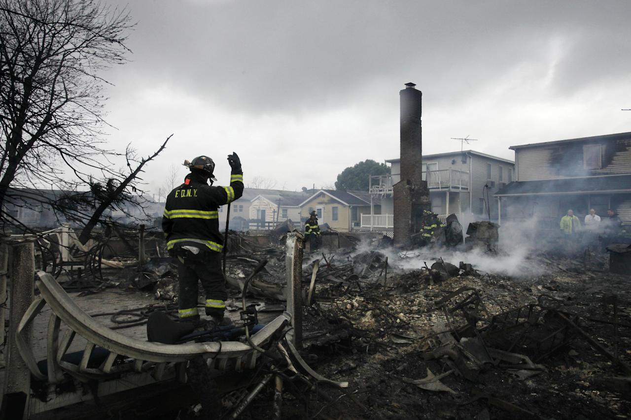 A fire fighter surveys the smoldering ruins of a house in the Breezy Point section of New York, Tuesday, Oct. 30, 2012. More than 50 homes were destroyed in a fire which swept through the oceanfront community during superstorm Sandy. (AP Photo/Mark Lennihan)