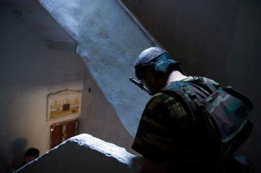 A rebel from the Free Syrian Army (FSA) stands in the stairwell of a building being used as an access route