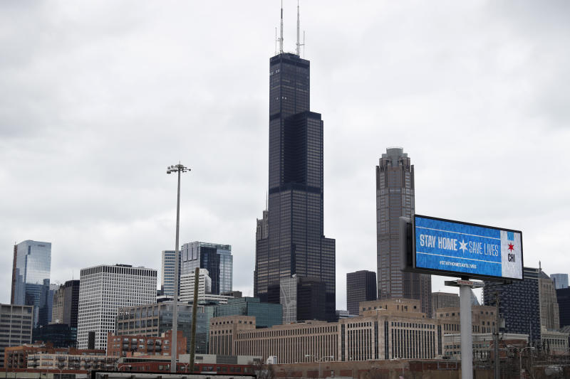 A public service message Stay Home Saves Lives is seen against the Chicago skyline Monday, March 30, 2020. The new coronavirus causes mild or moderate symptoms for most people, but for some, especially older adults and people with existing health problems, it can cause more severe illness or death. (AP Photo/Charles Rex Arbogast)