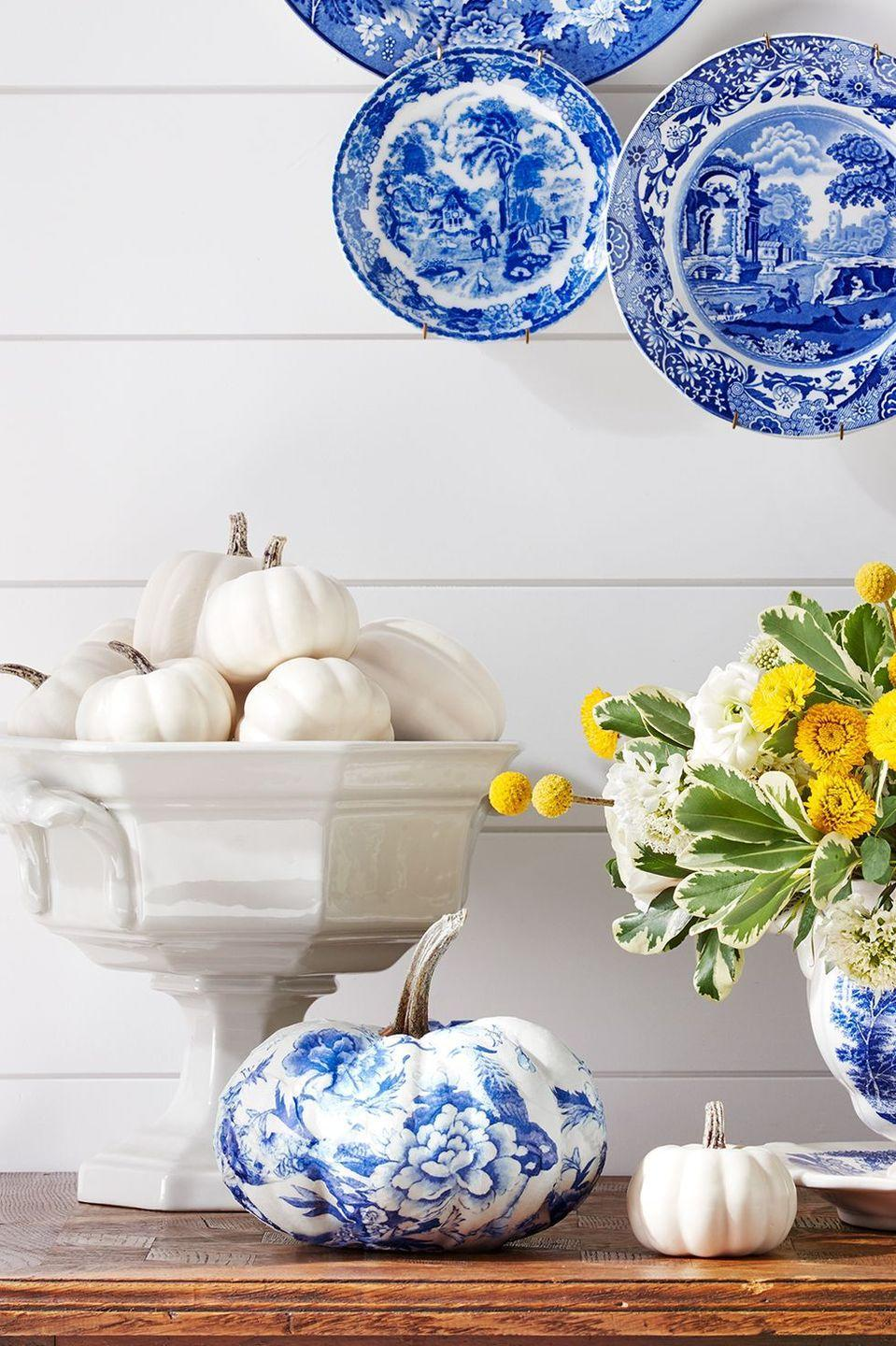 <p>If you're obsessed with interior design, this chinoiserie painted pumpkin idea is for you. To amp up the look, pair the centerpiece with dishware of the same style.</p>