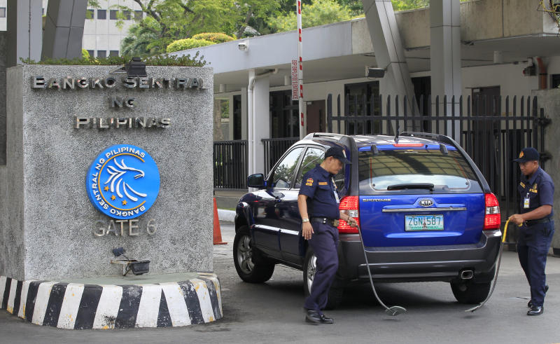 FILE PHOTO: Security guards inspect a vehicle entering the main gate of Bangko Sentral ng Pilipinas (Central Bank of the Philippnes) in Manila, Philippines March 23, 2016. REUTERS/Romeo Ranoco