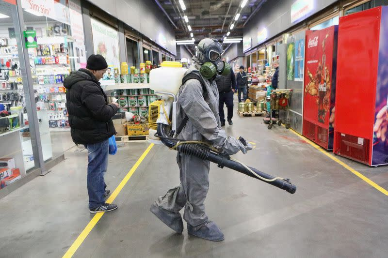 A specialist wearing protective gear sprays disinfectant inside the market in Moscow