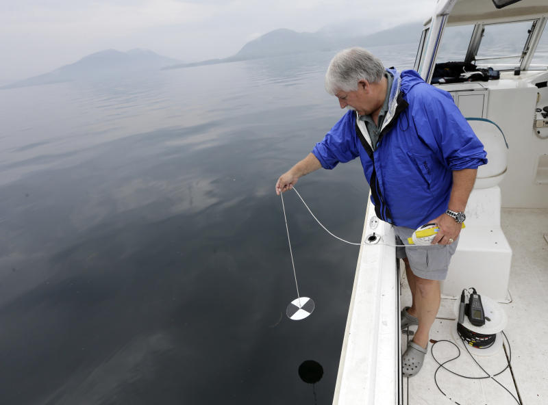 """Larry Eichler, a researcher scientist for Rensselaer Polytechnic Institute's Darrin Fresh Water Institute, lowers a Secchi disk into Lake George to test light penetration on Wednesday, June 26, 2013, in Bolton Landing, N.Y. An unprecedented project to turn New York's Lake George into the """"smartest lake in the world"""" is being launched to monitor the lake from its sun-dappled shores to its dark depths in hopes of keeping the Adirondack attraction pristine. (AP Photo/Mike Groll)"""