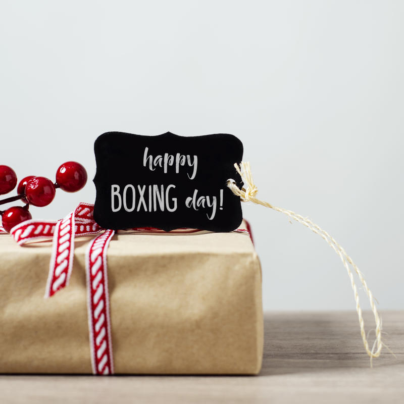 closeup of a cozy rustic gift, wrapped in kraft paper and tied with a red and white ribbon, ornamented with artificial red berries, and a black signboard with the text happy boxing day written in it
