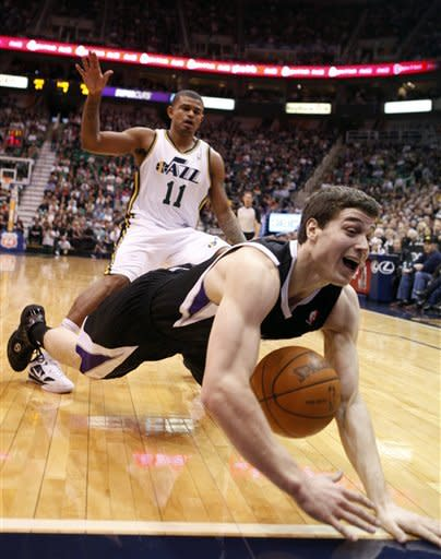 Sacramento Kings guard Jimmer Fredette (7) falls out of bounds while defended by Utah Jazz guard Earl Watson (11) during the first half of an NBA basketball game, Saturday, Jan. 28, 2012, in Salt Lake City. (AP Photo/Jim Urquhart)