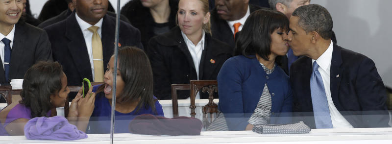 President Barack Obama kisses first lady Michelle Obama as their daughters Sasha, left, and Malia, second from left, look on during the Inaugural parade, Monday, Jan. 21, 2013, in Washington. Thousands marched during the 57th Presidential Inauguration parade after the ceremonial swearing-in of President Barack Obama. (AP Photo/Gerald Herbert)