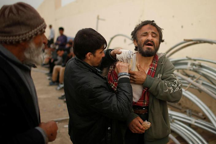 <p>A displaced Iraqi who had fled his home helps his wounded brother as Iraqi forces battle with Islamic State militants, in western Mosul, Iraq, April 11, 2017. (Suhaib Salem/Reuters) </p>