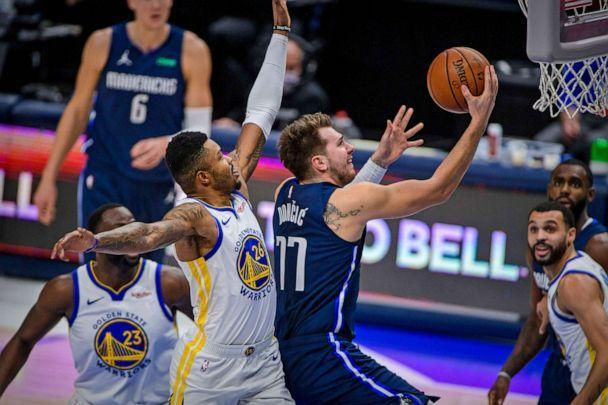 PHOTO: Dallas Mavericks guard Luka Doncic (77) drives to the basket past Golden State Warriors forward Kent Bazemore (26) and forward Draymond Green (23) during the first quarter of the game at the American Airlines Center in Dallas, Feb 6, 2021. (Jerome Miron/USA TODAY Sports via Reuters)