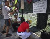 Hialeah resident Alison Kairuz, right, bows her head in prayer after pinning her hand-made sign to the fence in support of families and friends who lost love ones at the memorial site for victims of the partially collapsed South Florida condo building Champlain Towers South, in Surfside, Fla., Sunday, July 4, 2021. (Carl Juste/Miami Herald via AP)