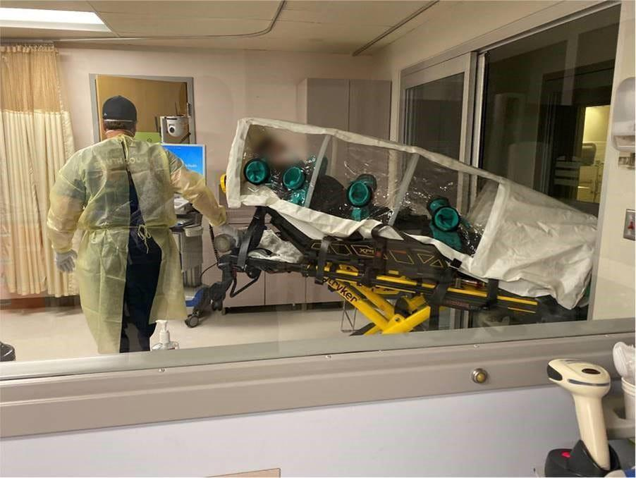 """The first known COVID-19 patient in the U.S. was confirmed in Snohomish County, Wash., on Jan. 20, 2020. The patient is seen here being transported in an isopod to Providence Regional Medical Center in Everett. A member of the hospital's """"BEST Team"""" (Bio-containment, Evaluation and Specialty Treatment team) helps care for the patient."""